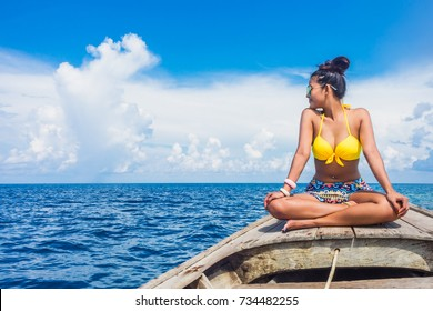 Traveler woman in bikini relaxing on wooden boat and looking destination island , Andaman sea, Mu Koh Surin national park, Phangnga, Travel in Thailand, Summer holiday and vacation trip