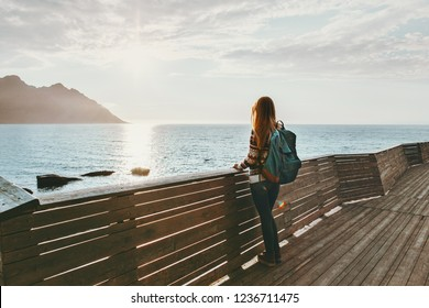 Traveler woman contemplating standing alone on bridge travel lifestyle vacations outdoor solitude emotions sunset sea view