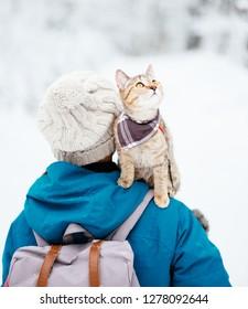 Traveler woman with cute cat on her shoulder walking in winter outdoor.
