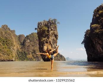 Traveler woman doing yoga fitness exercise on sea beach in front of famous tourist destination landmark James Bond island in Thailand, Asia