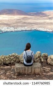 Traveler woman enjoying beautiful seascape at viewpoint on island. Travel concept. La Graciosa Island, Mirador del Rio, Lanzarote, Canary Islands.