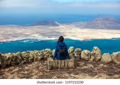 Traveler woman enjoying beautiful seascape at viewpoint on island. Travel concept. Winter in Canary Islands