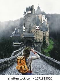Traveler woman in hat walking near castles in Germany, Eltz. Beautiful view of famous Eltz Castle.
