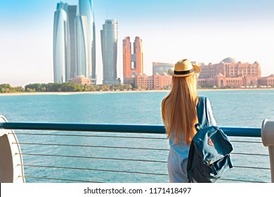 Traveler woman looking at Emirates Palace and skyscrapers of Abu Dhabi. Abu Dhabi is the capital and the second most populous city of the United Arab Emirates