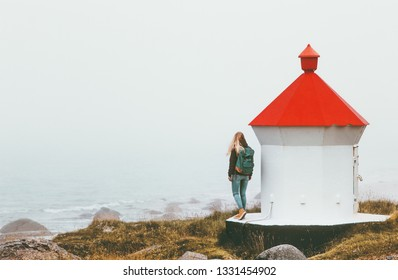 Traveler woman near lighthouse enjoying foggy sea view solo traveling lifestyle journey adventure outdoor solitude emotions