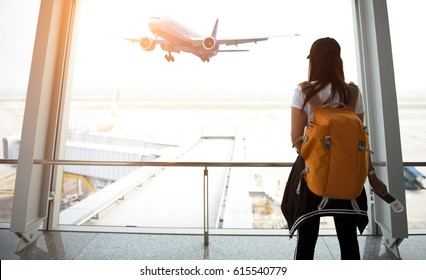 Traveler woman plan and backpack  see airplane flight at the airport glass window, girl tourist happy hold bag and waiting luggage in hall airplane departure.  Business people trip and Travel Concept