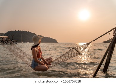 Traveler woman relax on hammock in the sea between sunset at the beach
