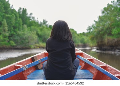 Traveler woman relaxing on the boat and looking around the mangrove forest , Ecotourism style.