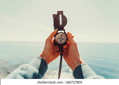Traveler woman searching direction with a compass on background of sea. Point of view shot