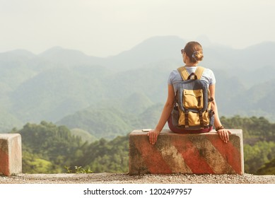 Traveler woman sits at the edge of the road on a road concrete barrier and looks at a mountain landscape.