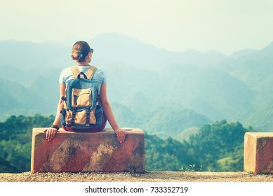 Traveler woman sits at the edge of the road on a road concrete barrier and looks at a mountain landscape.Mountains scenic, travel to Asia, summer holiday concept.
