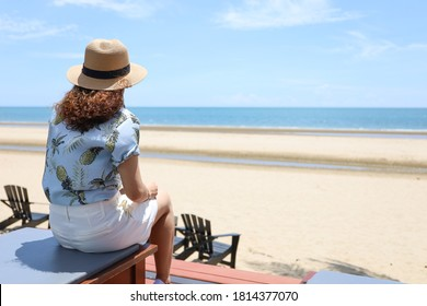 a traveler woman sitting on the chair in font of the beautiful sea beach in Thailand, summer vacation holiday trip relaxing