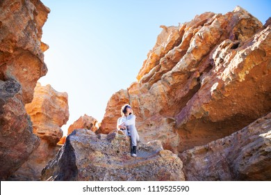 Traveler woman sitting on mountain in canyon. National park of Tenerife, Canary Islands, Spain