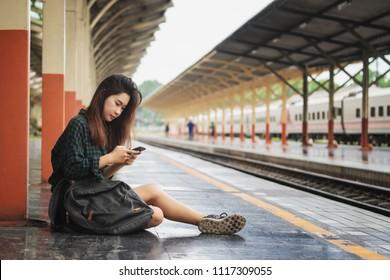 Traveler woman sitting and waits train on railway platform