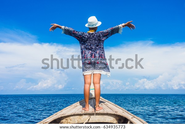 Traveler woman standing on wooden boat her arms open feeling freedom, Andaman sea, Mu Koh Surin national park, Phangnga, Thailand