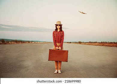 Traveler woman stands on road with vintage suitcase, airplane in sky. Space for text
