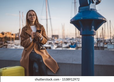 Traveler woman with suitcase holding mobile phone in evening port Barcelona. Girl tourist in glasses using smartphone technology online gadget cellphone. Digital internet lifestyle mockup