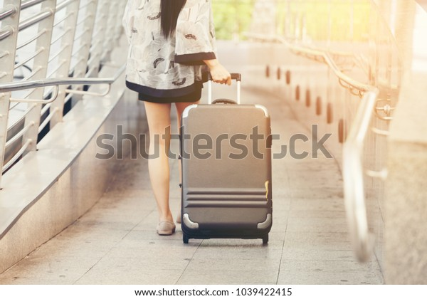 Traveler woman with a suitcase walking away with luggage on train station platform.transportation concept