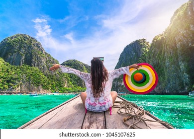 Traveler woman in summer dress joy relaxing on wooden boat, Maya beach, Phi Phi island, near Phuket, Krabi, Travel Thailand, Beautiful destination place Asia, Summer holiday outdoor vacation trip