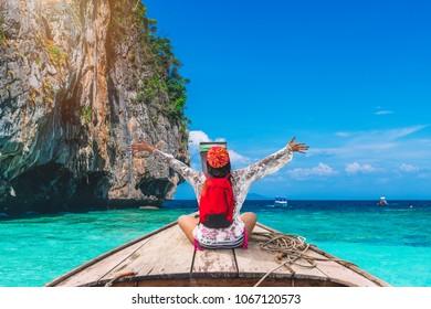Traveler woman in summer dress joy relaxing on wooden boat, Maya beach, Phi Phi island, near Phuket, Krabi, Travel nature in Thailand, Beautiful destination place Asia, Summer holiday vacation trip
