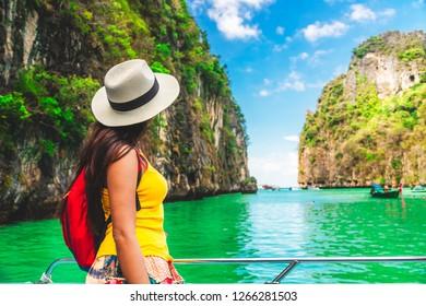 Traveler woman in summer dress relaxing on boat looking beautiful natural Pileh lagoon Krabi, Water travel Phuket Thailand beach, Tourist girl on summer holiday vacation, Tourism destination Asia trip