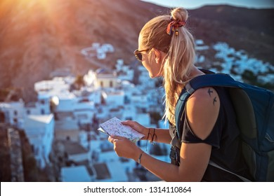 Traveler woman in trip to high mountins, pretty blond girl with map in hands and backpack searching the right way, enjoying view of mountainous city, active summer vacation
