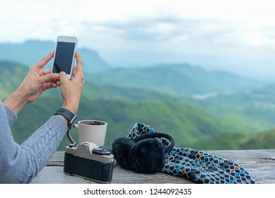 Traveler woman using smartphone and drinking  coffee and tea and take a photo and relax in sun sitting outdoor in sunshine light enjoying her warm morning at balcony house, winter season.