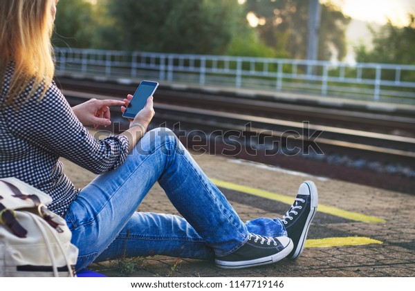 Traveler woman using a smartphone during a waiting for a train on railroad station. Backpacker wearing jeans and sneaker