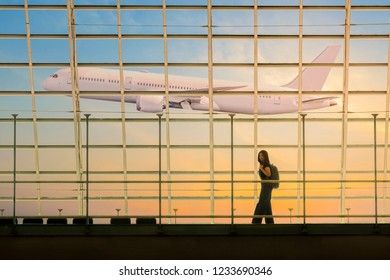 Traveler woman walking with backpack near window at the airport and airplane on background, Beautiful sun light and sky. Concept of emotional travel around the world