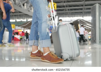 Traveler woman wear fashion jeans standing with a suitcase in airport terminal