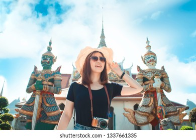 Traveler women enjoying with Giants statue front of the church at Wat Arun temple, Asian travel concept.