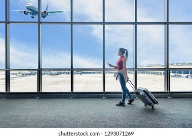 Traveler women plan and backpack see the airplane at the airport glass window. Asian tourist hold bag passport , board pass luggage in hall airplane departure. Travel and Holiday vacations Concept.