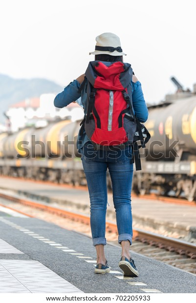Traveler women walking alone Carrying luggage and waits train on railway station.Beautiful young woman traveling. select and soft focus