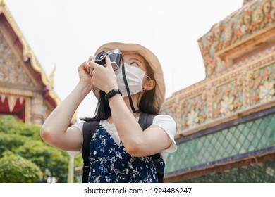 Traveler young asian woman or girl use camera take photo at temple, city tourism, wear face mask for prevention pandemic Backpacker tourist, holiday trip, summer or vacation concept.