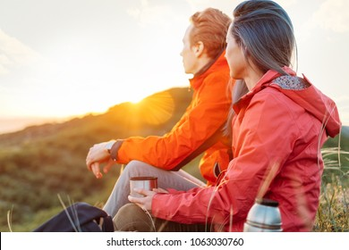 Traveler young couple resting with cup of hot drink in summer mountains and enjoying view of sunset light.