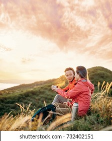Traveler young couple resting on picnic in the mountains at sunset.