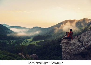 Traveler young man sitting on rocky stone and enjoying view of sunset in the mountains. Toned image
