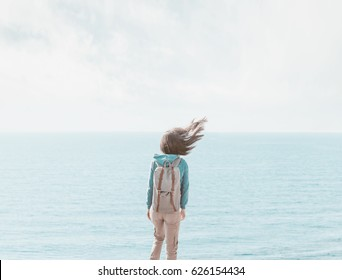 Traveler young woman with backpack standing on background of sea in windy weather, her hair fluttering in the wind, rear view.
