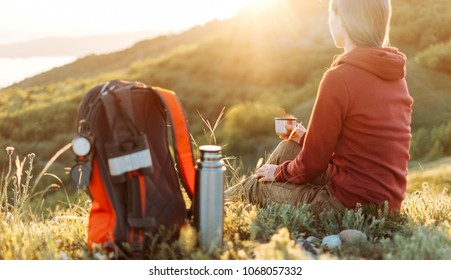 Traveler young woman resting with cup of hot tea in the mountains at sunset.