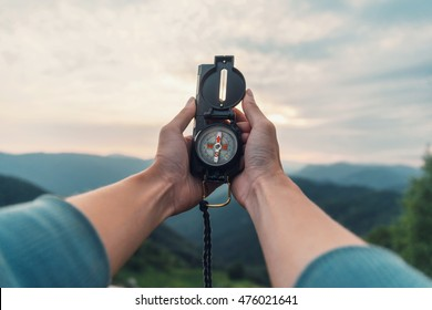 Traveler young woman searching direction with a compass in summer mountains. Point of view shot