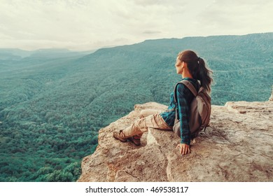 Traveler young woman sitting on edge of cliff and looking on mountains in summer. Toned image