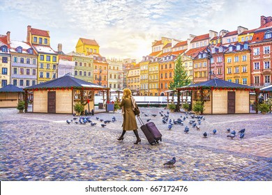 Traveler young woman walking with luggage on the Old Town Square with the Christmas market in Warsaw in the winter, Poland.