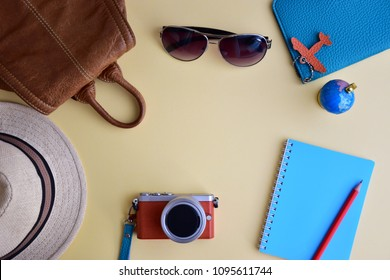 Traveler's accessories for trip planning  flay lay on light yellow background with brown leather bag, blue notepad, red pencil, glasses, passport holder and camera (copy space for text)