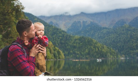 Travelers in checkered red shirts walk by the lake. Dad and eight-month-old son enjoy the view of the mountains and the forest. The child sits in the arms of his father