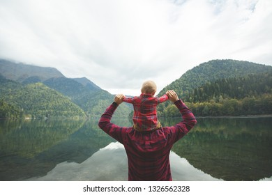 Travelers in checkered red shirts walk by the lake. Dad and eight-month-old son enjoy the view of the mountains and forest. The child sits on the shoulders of his father