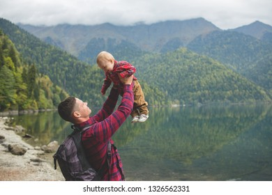 Travelers in checkered red shirts walk by the lake. Dad and eight-month-old son enjoy the view of the mountains and the forest. A man holds the baby in his arms
