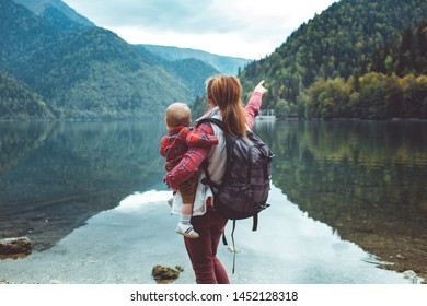 Travelers in checkered red shirts walk by the lake. Mother and eight-month-old son enjoy the view of the mountains and the forest.