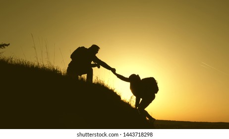 travelers climb the cliff holding hand. teamwork of business people. Happy family on vacation. traveler man extends his hand to a girl climbing to the top of hill. tourists hug on top of mountain