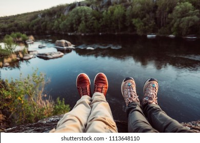 Travelers couple hiking boots on mountain near river on nature background. Man and woman family trekking shoes. Pair sitting and making feet selfie on beautiful landscape with forest.