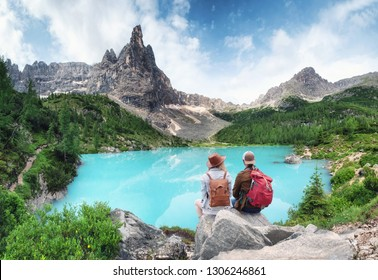 Travelers couple look at the mountain lake. Travel and active life concept with team. Adventure and travel in the mountains region in Dolomite alps, Italy
